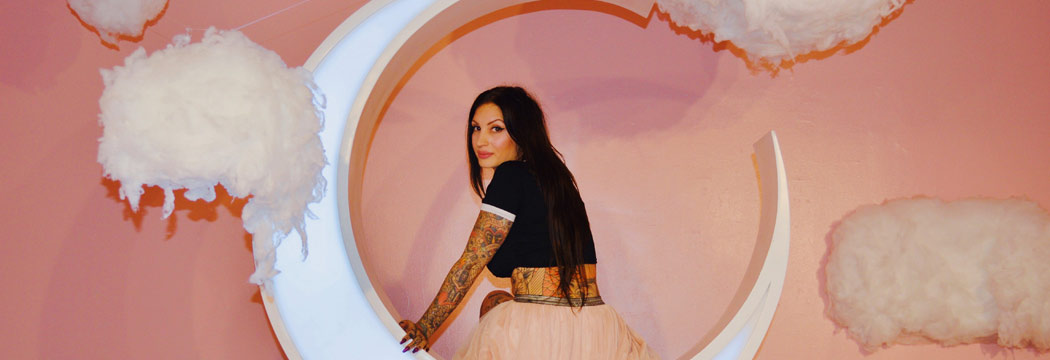 Tattoo artist Jessica Valentine seated on a crescent moon stage prop