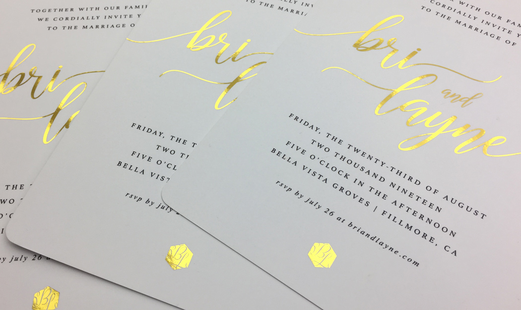 Luxurious wedding invitations featuring a simple, black-on-white design with bright gold foil highlights