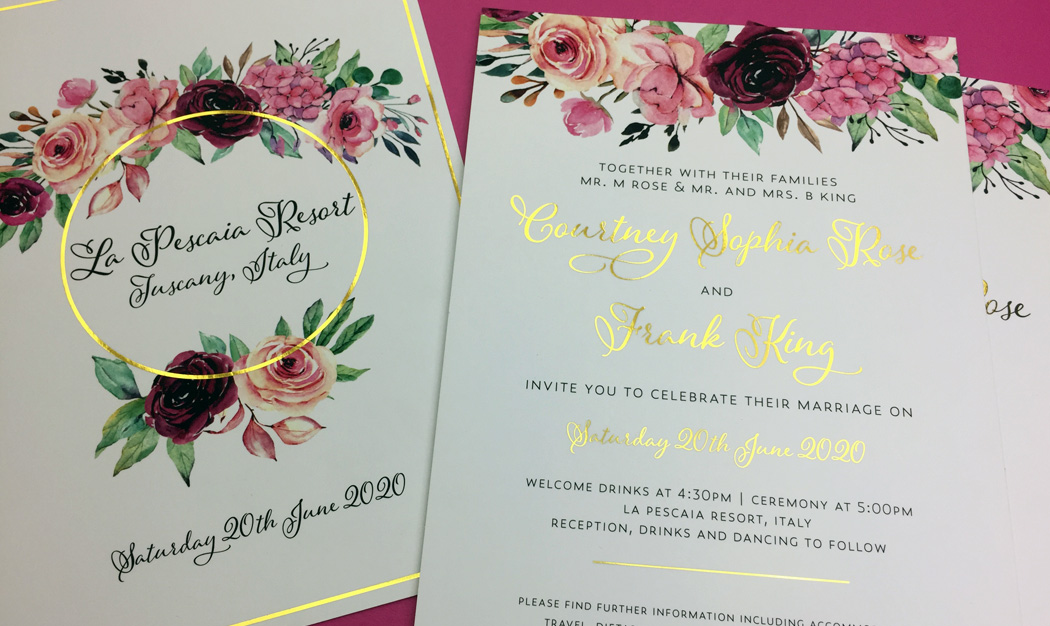 Floral wedding invitation cards featuring bright gold foil print on a wreath of pink blooms