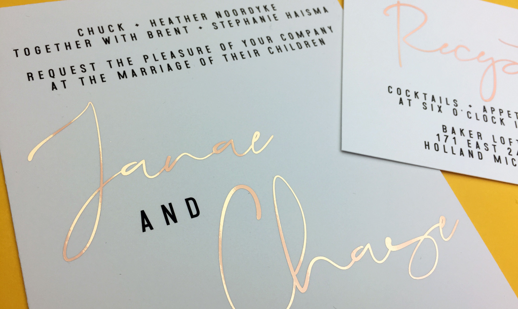 Luxurious white wedding invitation cards, featuring the names of the couple in bright rose gold foil print