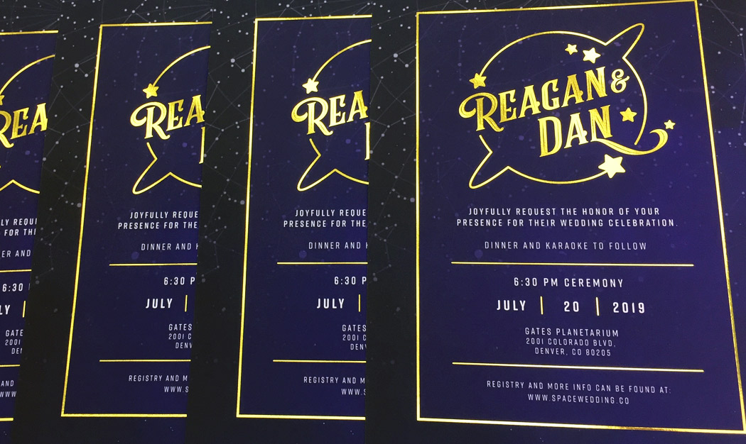 Dark, galaxy-themed wedding invitation cards, featuring bright gold foil print
